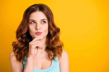 Photo of sly fascinating attractive pretty sweet girlfriend wearing teal tank-top touching chin with her hand while isolated with vivid color yellow background Фото со стока