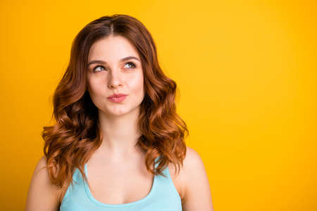 Photo of charming attractive nice cute interested girlfriend wearing teal singlet thinking on something sly while isolated over yellow background