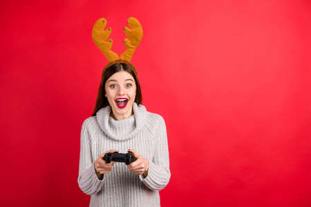 Childish lady playing games in xmas eve wear head deer horns and knitted sweater isolated red background