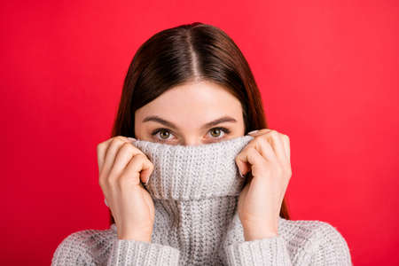 Pretty lady hiding half facial expression with warm collar of knitted sweater isolated on red background Фото со стока