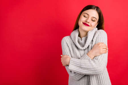 Pretty overjoyed lady with closed eyes touching soft knitted jumper isolated on red background