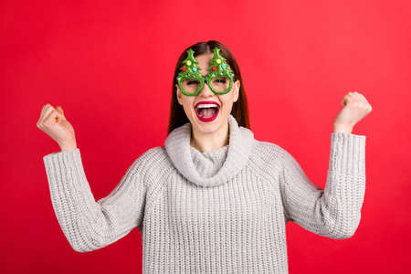 Photo of amazing lady meeting guests on party overjoyed wear xmas specs and knitted pullover isolated red background Фото со стока