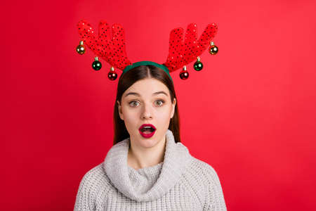 Photo of amazing speechless lady wear head horns and knitted sweater isolated red background