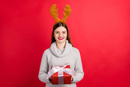 Photo of amazing lady with big giftbox wear head horns and knitted sweater isolated red background Фото со стока