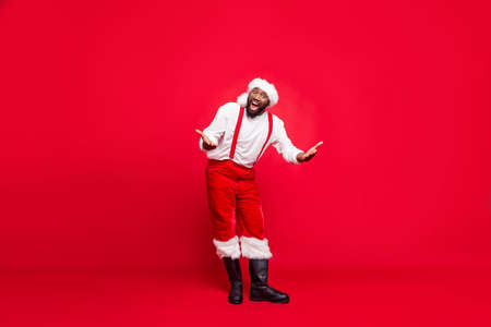 Full length photo of funky hipster afro american santa having xmas cap screaming wearing pants trousers isolated over red background 免版税图像