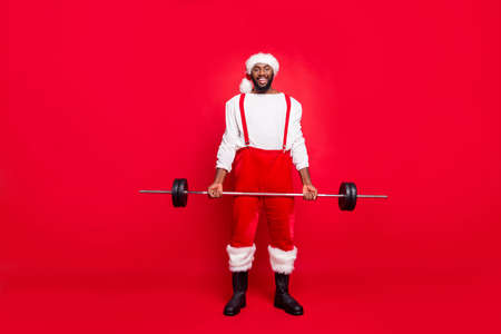Full length photo of positive african santa claus with black beard practicing holding sporty equipment wearing white pullover pants trousers isolated over red background