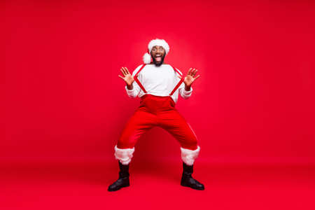 Full body photo of cheerful hipster afro american santa touching his suspenders screaming wearing trousers pants white pullover isolated over red background Foto de archivo