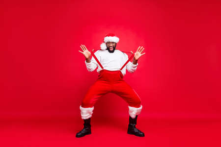 Full length photo of cheerful afro american santa with white sweater touching suspenders fooling wearing pants trousers isolated over red background