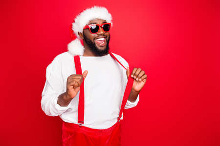 Turned photo of cheerful afro santa claus touching his suspenders posing wearing white pullover eyeglasses eyewear isolated over red background Stock Photo