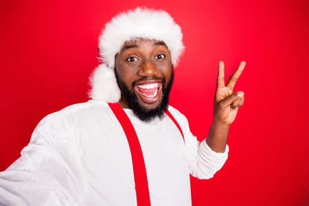 Close up photo of excited black christmas father in xmas hat enjoying memory take selfie making v-signs wearing white jumper isolated over red background