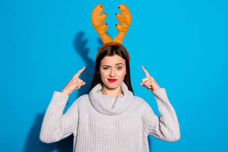 Photo of pretty lady indicating on her head angry with wearing toy horns knitted pullover isolated blue background