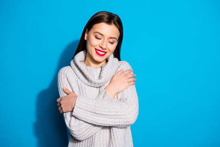Portrait of positive woman cuddling herself with eyes closed wearing grey woolen pullover isolated over blue background