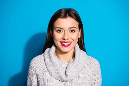 Portrait of pretty lady smiling looking wearing gray jumper isolated, over blue background 免版税图像 - 151053849