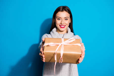 Portrait of lovely charming lady with toothy smile holding package giving wearing gray pullover isolated over blue background Фото со стока