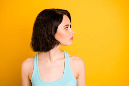 Close up photo of turned girlfriend pondering over someone standing away from her while isolated with yellow background 写真素材