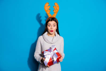 Photo of pretty lady with toy horns on her head holding red giftbox wear knitted pullover isolated blue background Фото со стока