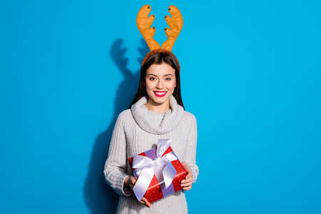 Photo of pretty lady with toy horns on her head holding red giftbox wear knitted pullover isolated blue background Standard-Bild