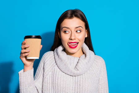 Portrait of lovely youth holding hot beverage espresso looking wearing gray sweater isolated over blue background Фото со стока