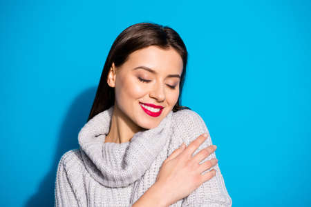 Portrait of lovely charming lady with closed eyes touching her gray pullover isolated over blue background