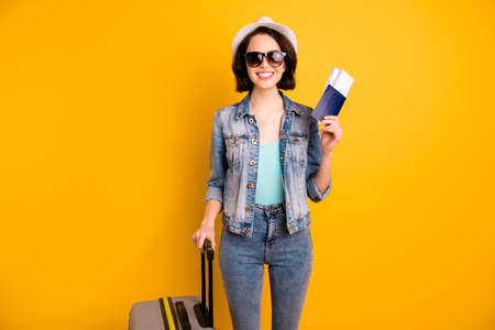 Photo of cheerful toothy attractive cute nice charming girlfriend wearing jeans denim jacket ready to leave for foreign lands while isolated with yellow background