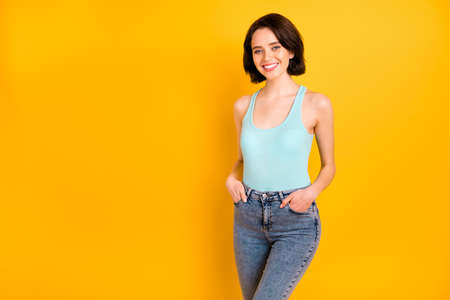 Photo of cheerful nice cute charming toothily smiling girl wearing jeans denim with her hands in pockets while isolated with yellow background 写真素材