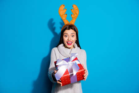 Petty lady with toy horns on her head giving red giftbox mommy wear knitted pullover isolated blue background Фото со стока