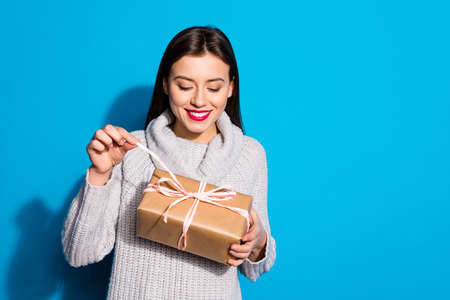 Portrait of cheerful lady pulling ribbon looking at package smiling wearing gray sweater isolated over blue background