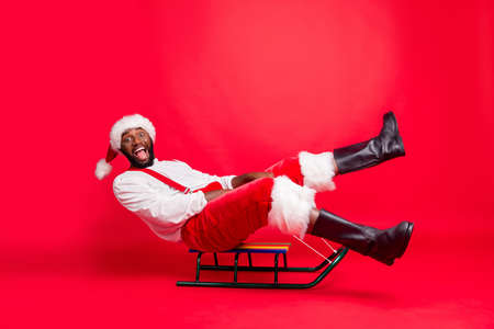 Full body profile side photo of amused african santa claus in xmas cap screaming sledding wearing white pullover pants trousers isolated over red background