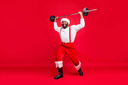 Full length photo of cheerful black santa claus in nicholas hat practice barbell wearing fashion white pullover pants trousers isolated over red background