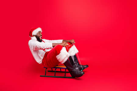 Full length photo of excited black santa claus in xmas cap screaming wow riding sledge wearing white pullover pants trousers isolated over red background 写真素材