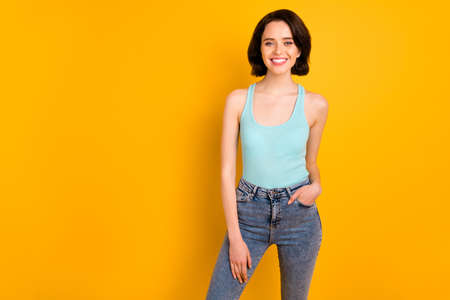 Photo of cheerful confident nice fascinating attractive girl confidently standing in front of camera isolated with yellow background