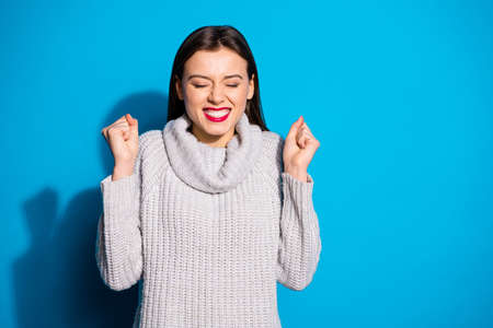 Portrait of cheerful girl closing her eyes raising fists wearing grey jumper isolated over blue background 写真素材