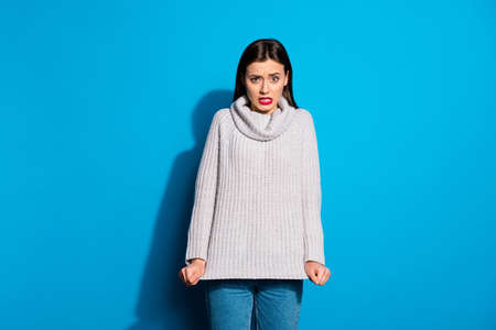 Portrait of disappointed lady looking touching her sweater isolated over blue background