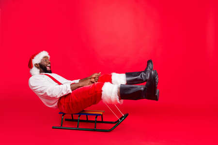 Full body profile side photo of amazed funny black santa claus riding toy sledges screaming wearing xmas pants trousers white sweater isolated over red background 写真素材