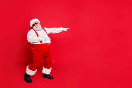Ganzkörperfoto von Comic Bully Fat übergewichtiger Weihnachtsmann mit lustigem dickem Bauchpunkt am Verlierer Lachen tragen Overalls Hosenträger haben stilvolle trendige Brillen einzeln auf rotem Hintergrund