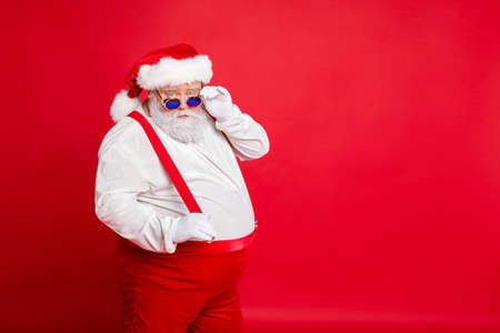 Portrait of handsome old funny fat overweight santa claus with big belly touch his retro specs choose naughty kids wear trousers pants isolated over red background Stock fotó