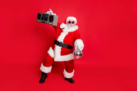 Full length photo of cute santa claus hold style sound boom box glittering ball dancing on noel party wear eyeglasses eyewear hat isolated over red background Banco de Imagens