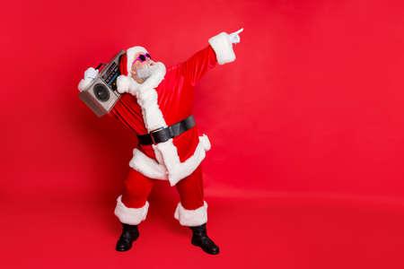 Foto lateral de perfil de longitud completa del divertido Papá Noel levanta los brazos, desgaste de la danza, gafas de moda con estilo, anteojos, sombrero, sombrero aislado sobre fondo rojo.