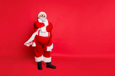 Full length photo of minded fat overweight santa claus bad guy with his hands crossed big abdomen choose naughty kids wear eyeglasses isolated over red background Stock fotó