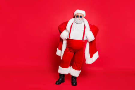 Full length photo of strict santa claus bad guy fat overweight with big belly decide choose naughty kids have stylish eyewear hat standing isolated over red background