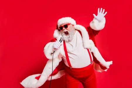Foto en primer plano de divertido vocalista salvaje cobarde gritando en el micrófono con guantes de abrigo de piel tirantes aislado fondo brillante