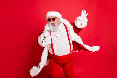 Portret fajnego śmiesznego tłuszczu z nadwagą Świętego Mikołaja z dużym brzuchem śpiewa piosenkę na imprezie świątecznej nosić styl stylowy modny kapelusz okulary na białym tle na czerwonym tle