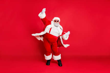 Full length size photo of carefree delightful rejoicing funky holly-jolly moving st nicholas father christmas big belly in suspenders traditional outfit fur trousers sunglass boots isolated background Reklamní fotografie