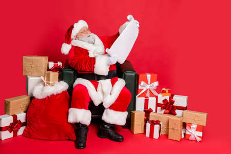 Kind generous funky fat overweight plump gray-haired bearded man sitting in chair post office reading wish list letter sending delivery winter isolated over bright vivid shine red background