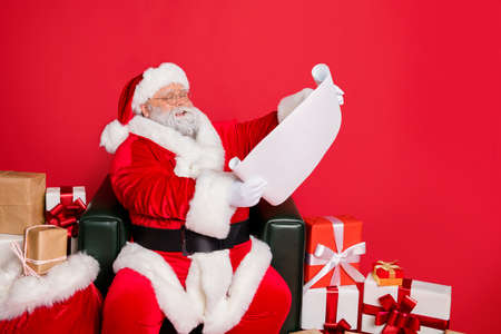 Portrait of his he nice cheerful kind generous fat bearded man St Nicholas reading address list clients wish want fairy miracle orders winter december isolated over bright vivid shine red background