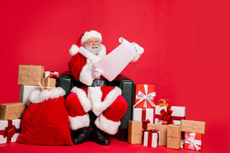Nice cheerful cheery hard-working fat bearded man St Nicholas sitting in armchair reading address list clients want fairy miracle orders winter isolated on bright vivid shine red background