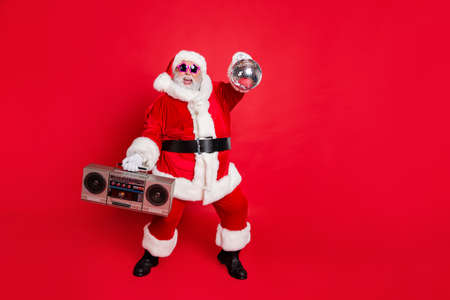 Full length photo of cheerful santa claus in headwear hat holding boom box glittering ball dancing on newyear party wearing style stylish eyeglasses eyewear isolated over red background