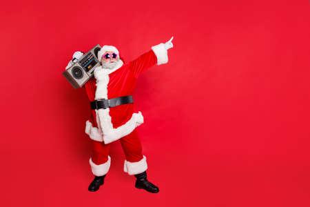 Foto completa del corpo di Babbo Natale carino divertente con scatola da discoteca boom sonoro che balla indossando occhiali stile occhiali copricapo cappello isolato su sfondo rosso
