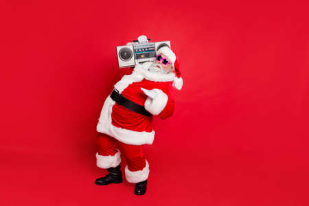 Full size photo of cool old stylish trendy santa claus in eyewear eyeglasses dancing holding audio sound cassette isolated over red background