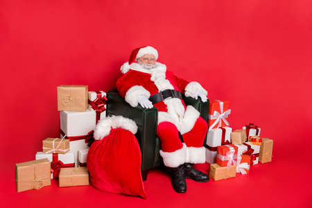 Photo of wise glad cute Father Christmas enjoy wait time and kid favorite winter days. Sitting near stack pile many lot wrapped boxes and large bag cap with dreamy presents isolated vivid background Stockfoto